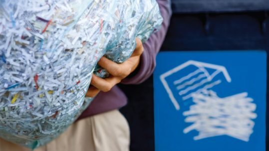 person holding bag of shredded paper going into a recycling bin
