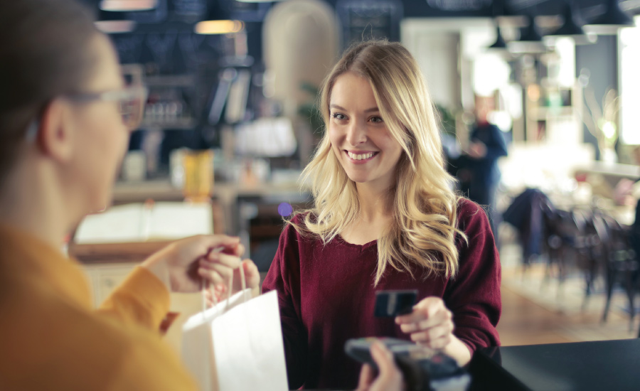 Young adult female at cash register paying for items with a debit card and smiling