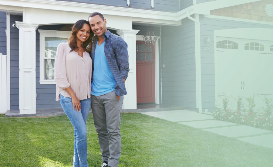 Young couple smiling in front of their newly purchased home