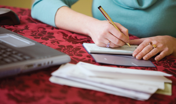 Closeup of a woman at a table paying bills and writing a check from a checkbook