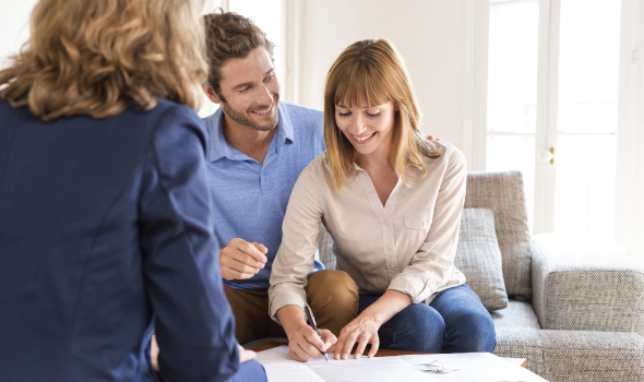 Young Couple with real estate agent eagerly buying a home